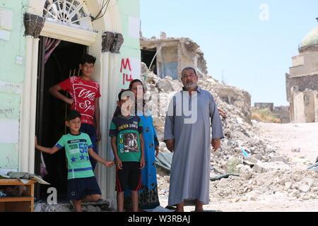(190717) -- di Mosul, luglio 17, 2019 (Xinhua) -- Laith Najim (1R) e i membri della sua famiglia in stand by davanti la porta di casa nella città vecchia a Mosul, Iraq, 14 luglio 2019. La guerra per liberare l Iraq di Mosul da uno Stato islamico (SI) gruppo militante ha ottenuto la vittoria per due anni, ma le sue gravi impatti ancora pesare sui residenti della città. Un grassroots campagna di raccolta fondi è stato avviato in cinese social media con schiacciante solidarietà, puntando a portare speranza alla guerra-ridden famiglie in Iraq di Mosul. Per andare con 'Funzione: Cinese grassroots donazioni portare speranza alla guerra-ridden fa Immagini Stock