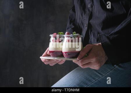 Donna in camicia nera tenendo in mano in casa dessert classica panna cotta con lampone e mirtillo bacche e jelly in vasi, decorata da una di menta Immagini Stock