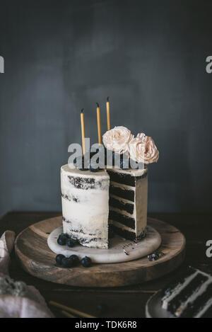 Lo strato di una torta di compleanno con torta al cioccolato e vaniglia glassa, completare con le candele. Immagini Stock
