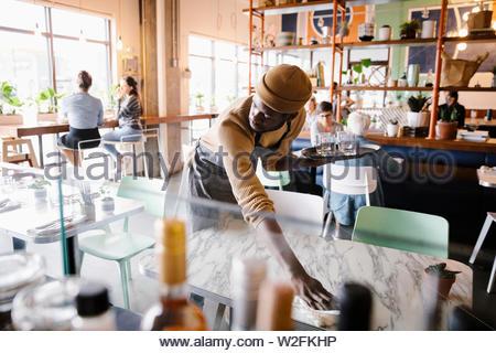 Lavoratore di sesso maschile tabella di pulizia in cafe Immagini Stock