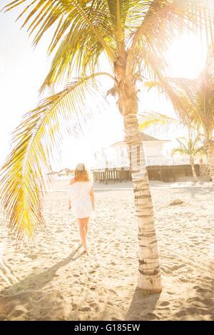 Lunghezza piena vista posteriore della metà donna adulta sulla spiaggia sotto il palm tree, Tenerife, Isole Immagini Stock
