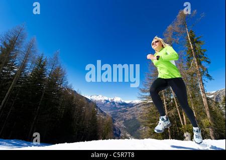 Una donna fare jogging in montagne innevate. Immagini Stock
