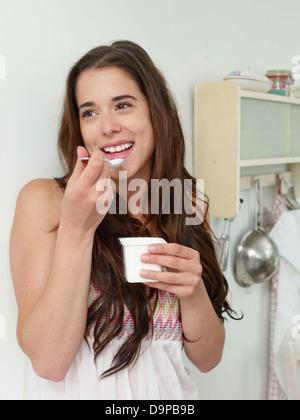 Bruna giovane donna mangiare yogurt Immagini Stock