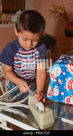 Un giovane bambino incarto regalo di Natale. Serie di 7 immagini. Signor © Myrleen Pearson ...Ferguson Cate Immagini Stock