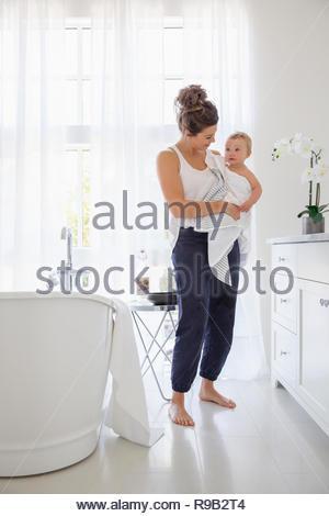 Azienda madre bimba in asciugamano dopo il bagno in stanza da bagno Immagini Stock