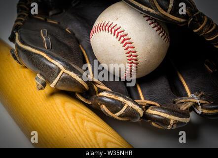 Un guanto di pelle nera con il baseball e il bat su sfondo bianco Immagini Stock
