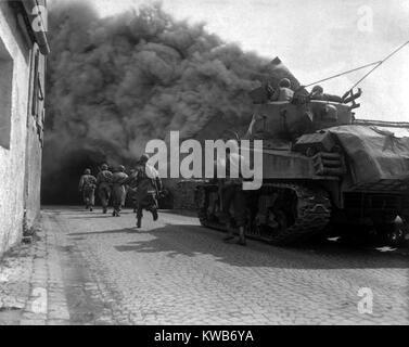 U.S. fanti che corre attraverso il pieno di fumo strade di Wernberg, Germania. 55Th corazzato battaglione di fanteria Immagini Stock
