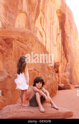 Un ragazzo e una ragazza su roccia al Parco Nazionale di Arches Immagini Stock