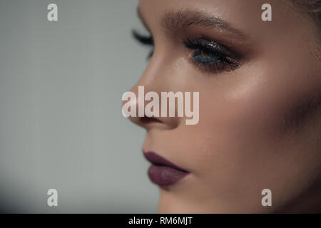 Faccia verticale nel profilo di una bellissima ragazza con trucco professionale su sfondo bianco Immagini Stock