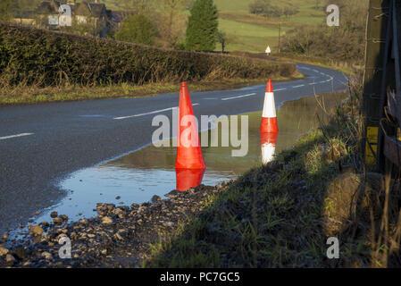 Traffico coni che indica di buche nascoste in una pozzanghera sulla strada di un paese, Dunsop Bridge, Clitheroe, Lancashire, Regno Unito Immagini Stock