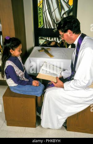 Sacerdote cattolico leggendo la Bibbia al bambino durante la riconciliazione. © Myrleen Pearson ....Ferguson Cate Immagini Stock