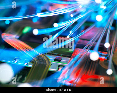 In fibra ottica i trefoli che trasportano i dati su una scheda a circuito elettronico del computer portatile Immagini Stock