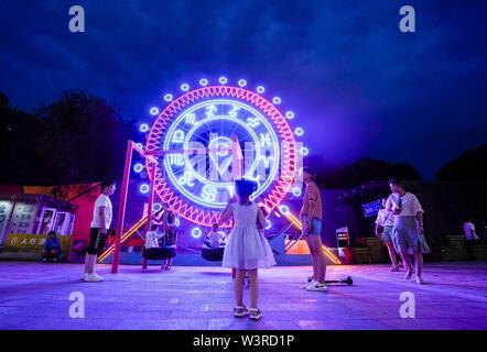Urumqi, della Cina di Xinjiang Uygur Regione autonoma. 14 Luglio, 2019. I bambini giocano nelle vicinanze di un illuminato installazione in Urumqi, a nord-ovest della Cina di Xinjiang Uygur Regione autonoma, luglio 14, 2019. Notte-economia di tempo è stato il prelievo in Urumqi a partire dal mese di luglio. Le persone si divertono a raffreddare le notti estive da shopping e degustazione del cibo. Credito: Zhao Ge/Xinhua/Alamy Live News Immagini Stock