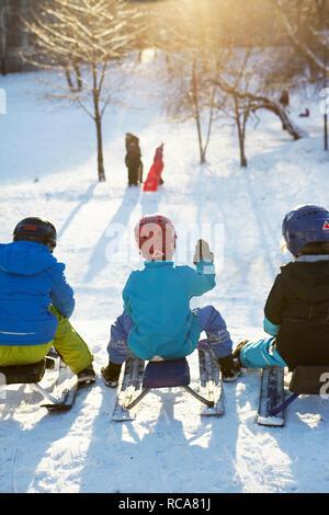 Bambini su scooter da neve in inverno Immagini Stock