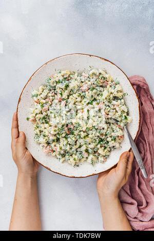 Donna che serve piatti vegetariani maccheroni insalata in una grande ciotola in ceramica Immagini Stock