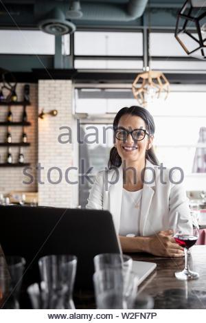 Ritratto fiducioso imprenditrice lavora al computer portatile e bere il vino al ristorante Immagini Stock