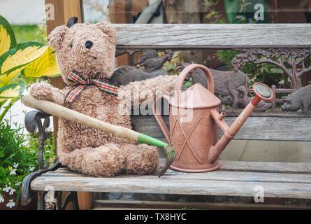 Vecchio orsacchiotto e annaffiatoio al di fuori di una serra su un display ad RHS Chatsworth flower show 2019. Chatsworth, Derbyshire, Regno Unito. Filtro vintage Immagini Stock