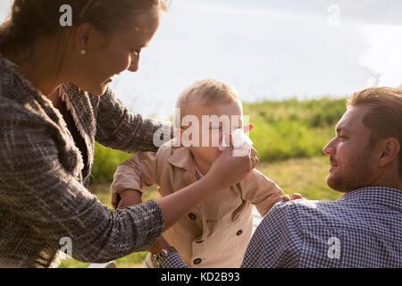 Figlio (18-23 mesi) soffia il naso Immagini Stock