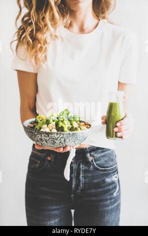 Una sana cena e pranzo. Donna in jeans e permanente tenendo vegane superbowl Buddha o ciotola con hummus, verdure, insalate fresche, fagioli, couscous e avo Immagini Stock