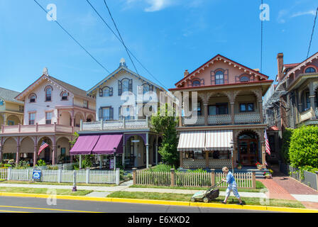 Stati Uniti d'America,New Jersey,Cape May, case vittoriane e persona la falciatura di prato anteriore. Immagini Stock