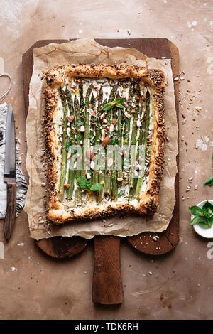Crostata di asparagi su carta pergamena su un tagliere Immagini Stock