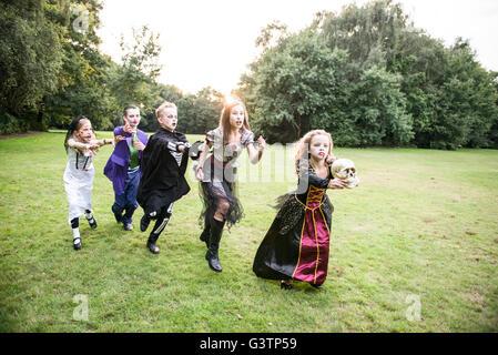Bambini inseguire una ragazza vestita come uno zombie prom regina per la notte di Halloween. Immagini Stock