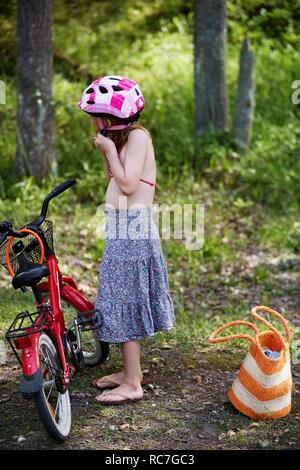 Vista laterale della ragazza mettendo sul ciclismo casco Immagini Stock