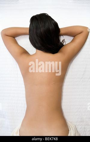 Donna sdraiata su un lettino da massaggio Immagini Stock