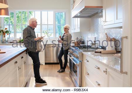 Coppia senior parlando in cucina Immagini Stock
