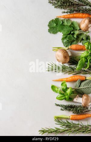 Varietà di cucina fresca erbe con mini carote e funghi champignon in fila su marmo bianco dello sfondo. Appartamento laico, spazio. Concetto di cucina a vista, cibo Immagini Stock