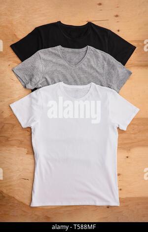 Pila di colore diverso mens T-shirt su sfondo di legno. Vedi verticale. Immagini Stock
