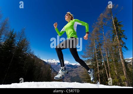 Una donna jogging attraverso innevate montagne d'inverno. Immagini Stock
