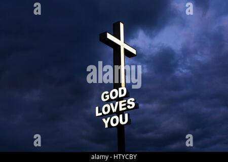 Dio vi ama firmare con croce illuminata contro un cielo tempestoso Immagini Stock