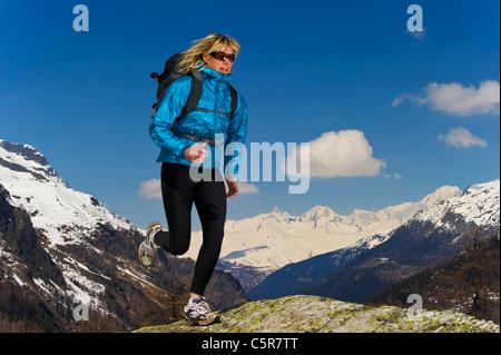 Esecuzione del pareggiatore attraverso montagne innevate. Immagini Stock