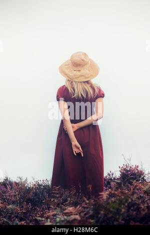 Una ragazza in un abito rosso è in piedi nel heather Immagini Stock