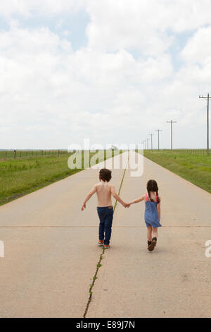 Fratello e Sorella e camminare lungo il marciapiede in paese Immagini Stock