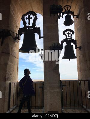 Una donna si reca presso il campanile di Caceres, Andalusia, Spagna Immagini Stock