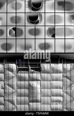 Un lavoratore a un piano dell'Elbe Philharmonic Hall di Amburgo tra la facciata finita e ponteggi. Immagini Stock