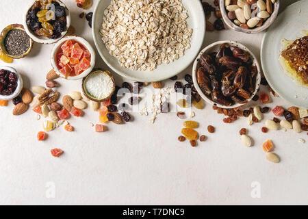 Varietà di frutta secca, noci, miele e fiocchi di avena in ciotole di ceramica per la cottura in casa sana colazione muesli muesli o barrette energetiche su bianco t Immagini Stock