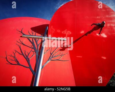 Un albero, una croce e una scultura di un uomo a piedi decorare un nir cuore rosso un monumento a Fatima, Portogallo Immagini Stock
