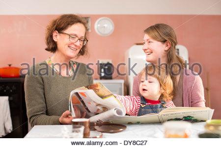 Nonna, madre e figli nella lettura di un libro per bambini Immagini Stock
