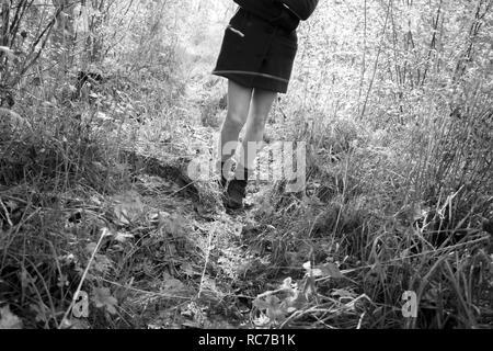 Le gambe della ragazza adolescente camminare in Prato Immagini Stock