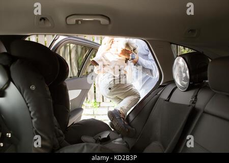 Padre tenendo figlio (18-23 mesi) al di fuori della vettura Immagini Stock