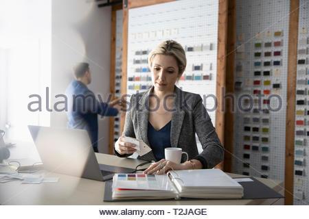 Femmina di interior designer guardando i campioni di vernice in design studio Immagini Stock