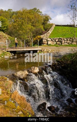 Irlanda del Nord, Co Down, Bassa Mournes, Crockbane, donna attraversando ponte pedonale a guado Cassy acqua Immagini Stock