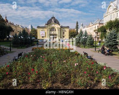 Splendidi edifici che circondano la piazza Teatralina in Chernivtsi, Ucraina. Le rose sono in fiore nel centro Immagini Stock
