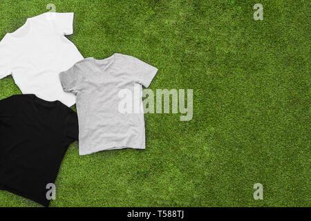 Casualmente disperse mens di colore diverso T-shirt su sfondo di erba. Vista orizzontale. Immagini Stock
