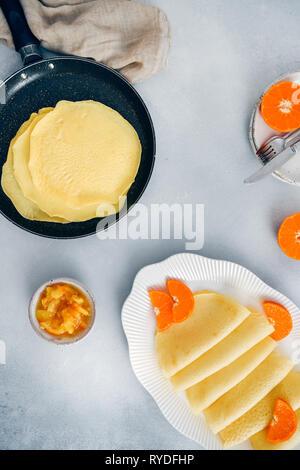 Senza glutine crepes in una padella antiaderente e in un bianco targhetta ovale guarnite con fettine di arancia, accompagnato da orange jam. Immagini Stock