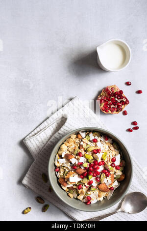 Ciotola di cereali per la prima colazione, semi, frutta a guscio e i semi di melograno; con copyspace. Immagini Stock