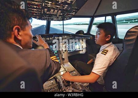 (190717) -- KUNMING, luglio 17, 2019 (Xinhua) -- uno studente (R) impara da un istruttore in un Airbus A320 del simulatore di volo durante un aviation-tema summer camp per la scuola elementare e media gli studenti di Kunming, a sud-ovest della Cina di Provincia di Yunnan, 17 luglio 2019. (Xinhua/Qin Qing) Immagini Stock